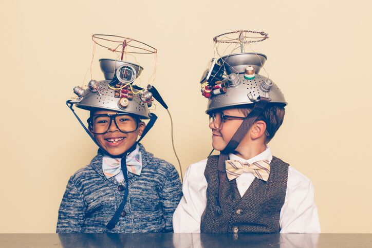 Photo of two smiling boys wearing homemade sci-fi style helmets on their heads (made out of metal colanders, wire and push buttons) that appear to be mind-reading devices.