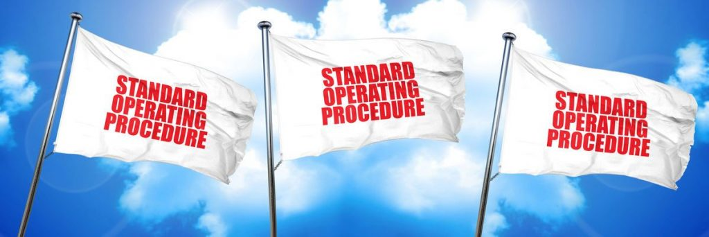 Three white flags with red words that say Standards Operating Procedure. The flags are waving in the air with a background of a blue sky and clouds.