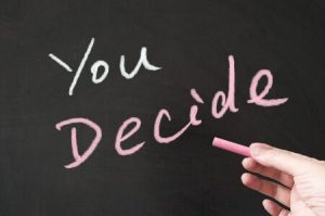 "A hand that is writing on the chalkboard ""You Decide"""